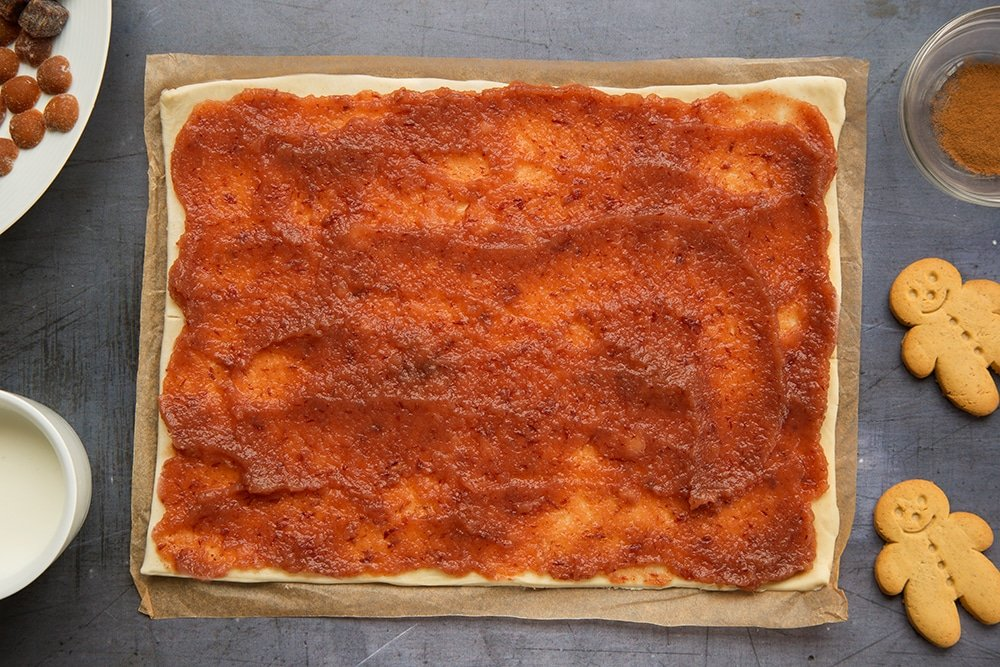 Puff pastry sheet topped with red applesauce