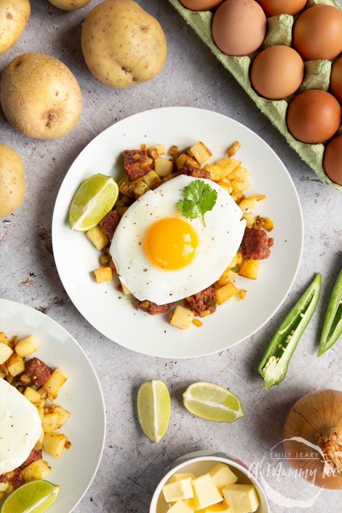 Curried corned beef hash topped with a fried egg, surrounded by raw ingredients