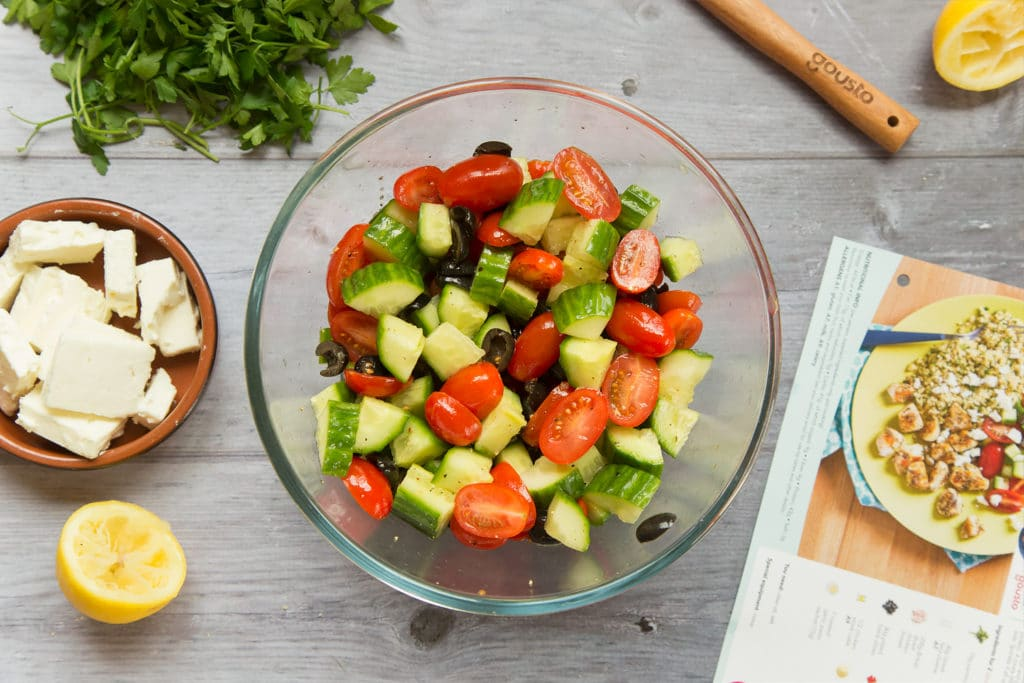 Seasoned cucumber, tomatoes and olives in a bowl