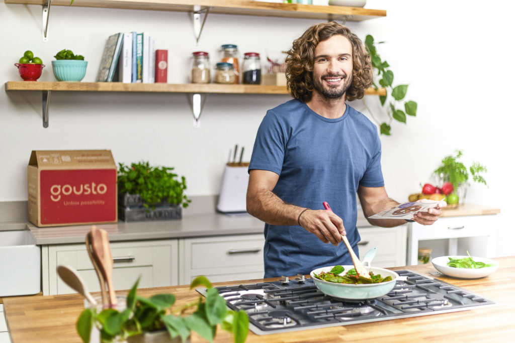 Joe Wicks cooking in a kitchen with a Gousto box in the background
