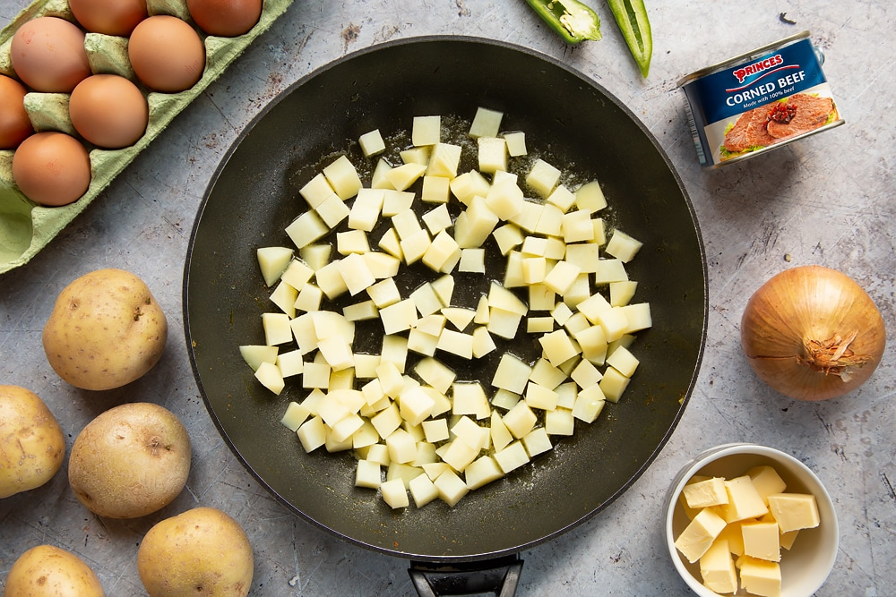 Parboiled potatoes, cubed, in a frying pan