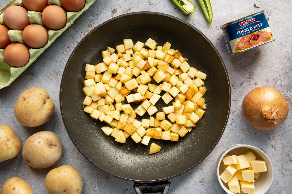 Golden potato cubes in a frying pan
