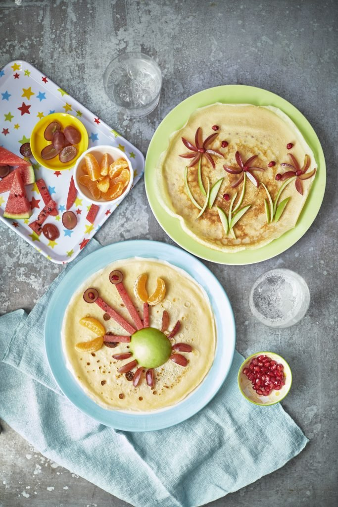 Overhead shot of Pancake Art served on a blue and green plate topped with fruits