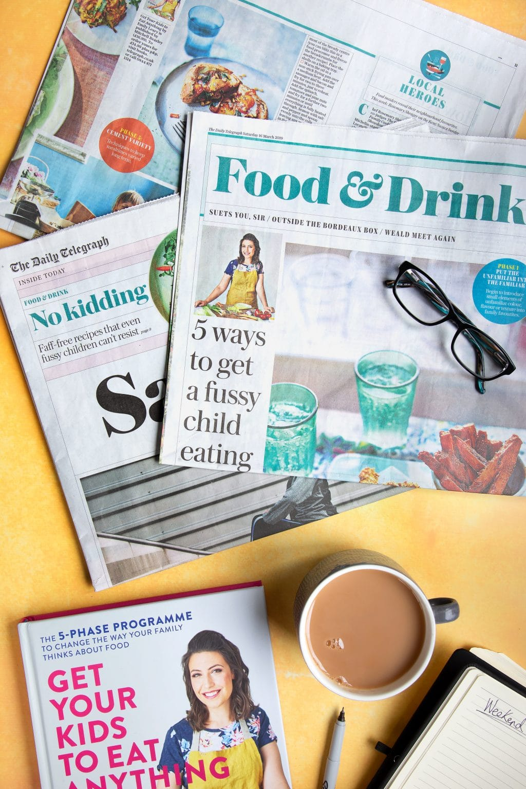 Overhead shot of glasses, newspapers, coffee, and Get Your Kids to Eat Anything cookbook