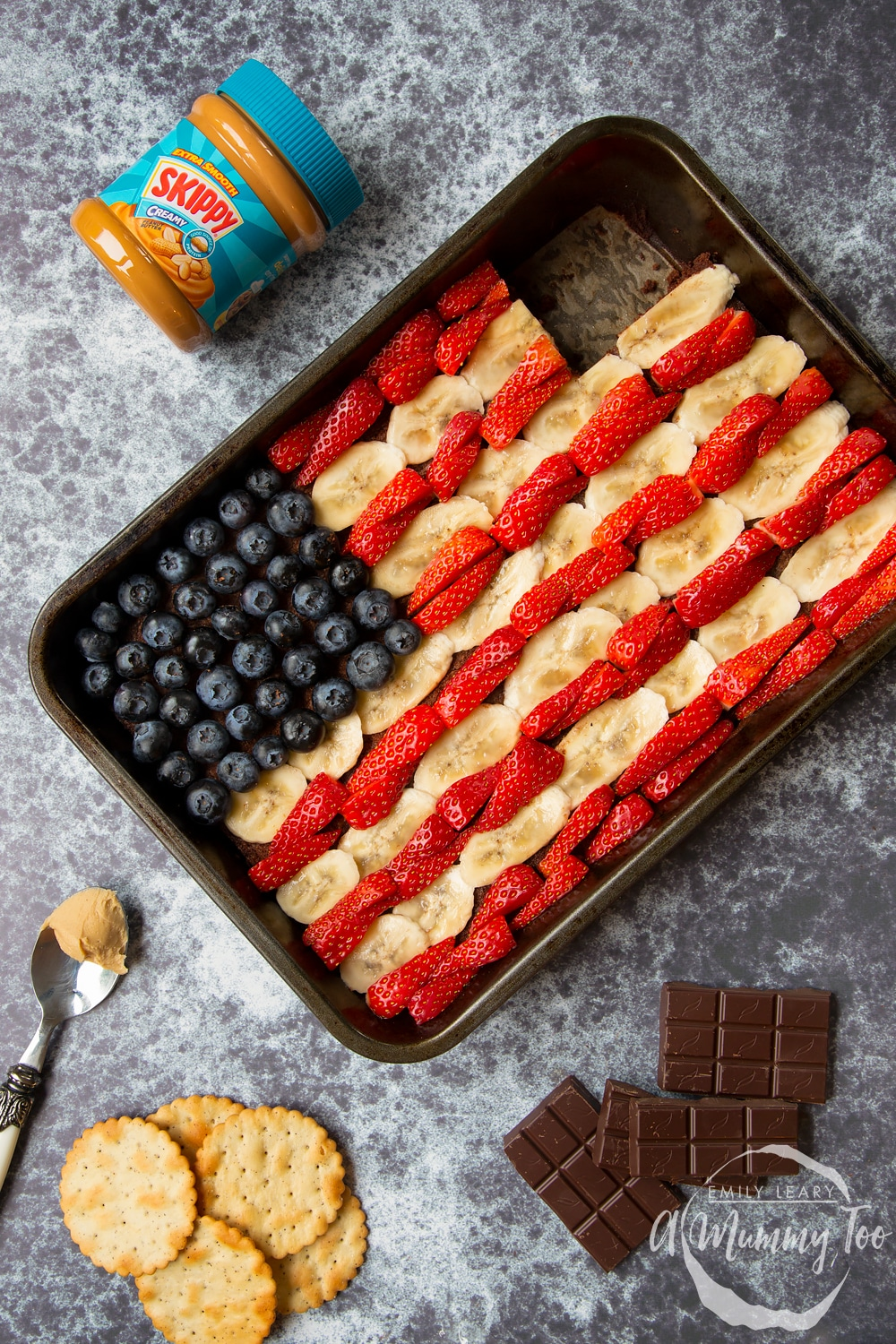 The decorated peanut butter brownies sheet pan with bananas strawberries and blueberries