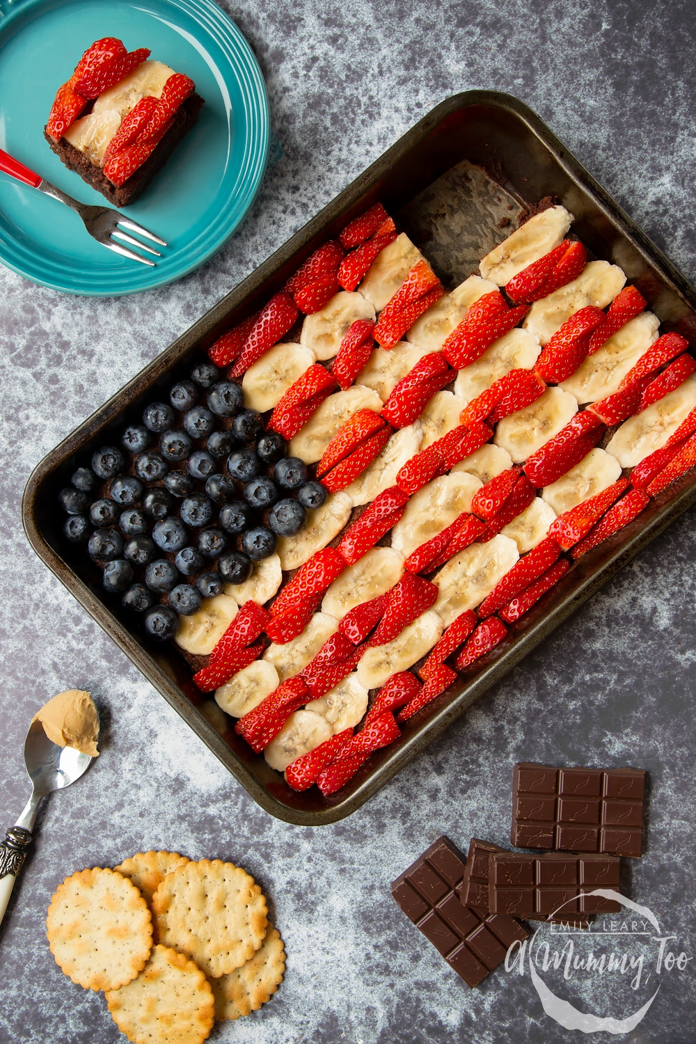 A plate with a section of the peanut butter brownies in the shape of the American flag for the 4th of July alongside the remaining peanut butter brownies tin.