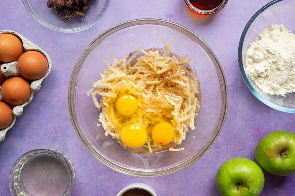 No junk apple and strawberry muffins - grated apple, eggs, maple syrup and oil in a bowl.