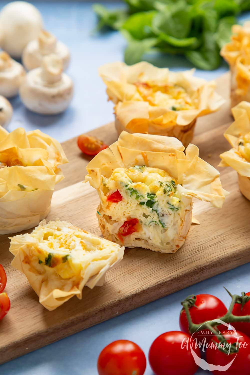 Filo pastry mini quiches - cut open to show the cooked filling with pieces of tomato and spinach.