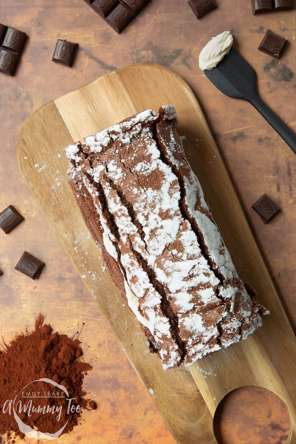 A fully rolled chocolate roulade arranged on a board.