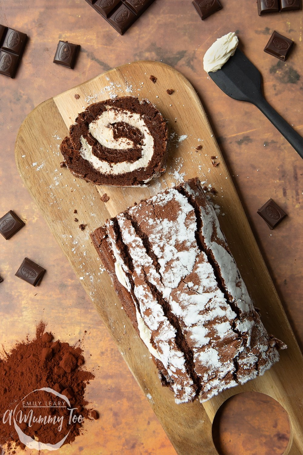 Mary Berry's chocolate roulade, shown from above, with a slice on a board.