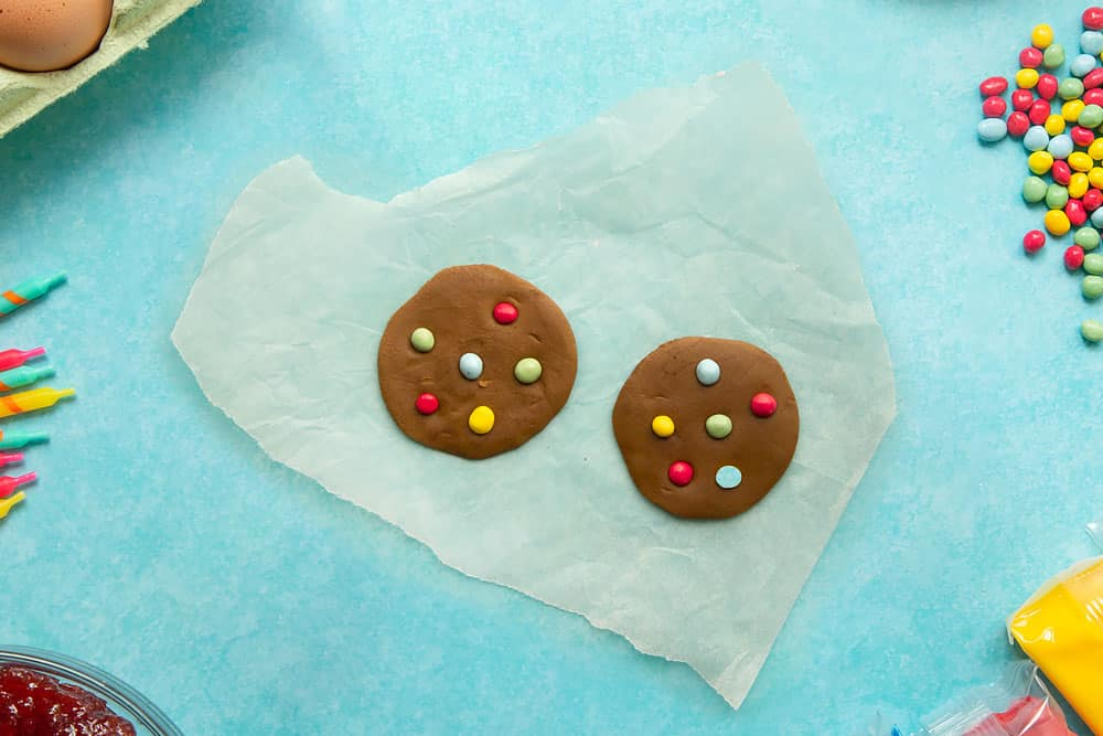 Chocolate sugar paste rolled out to form two small discs, with chocolate buttons pushed into the surface to resemble cookies