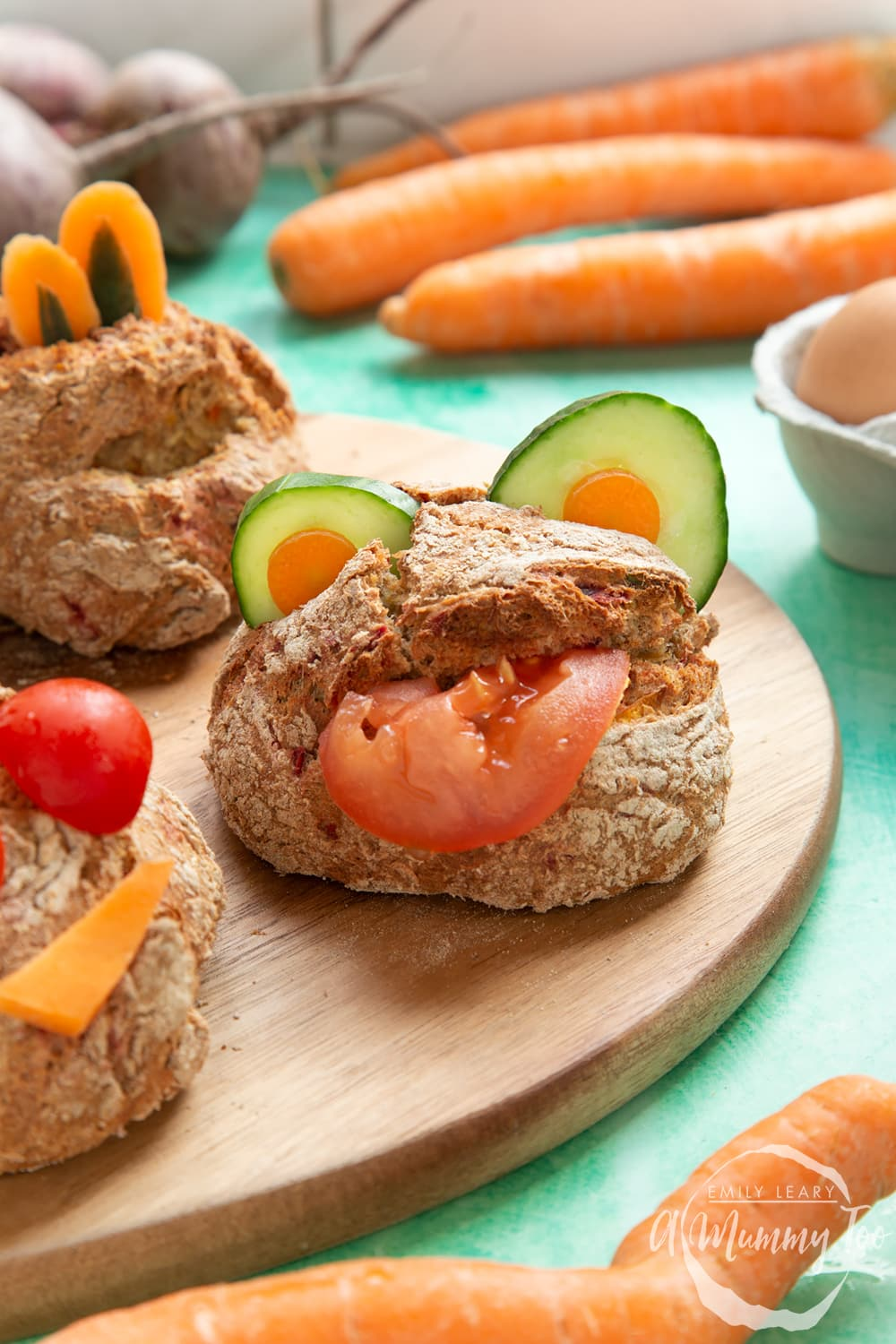 Vegetable soda bread rolls recipe - rolls arranged on a board, each decorated with vegetable slices to look like monsters.