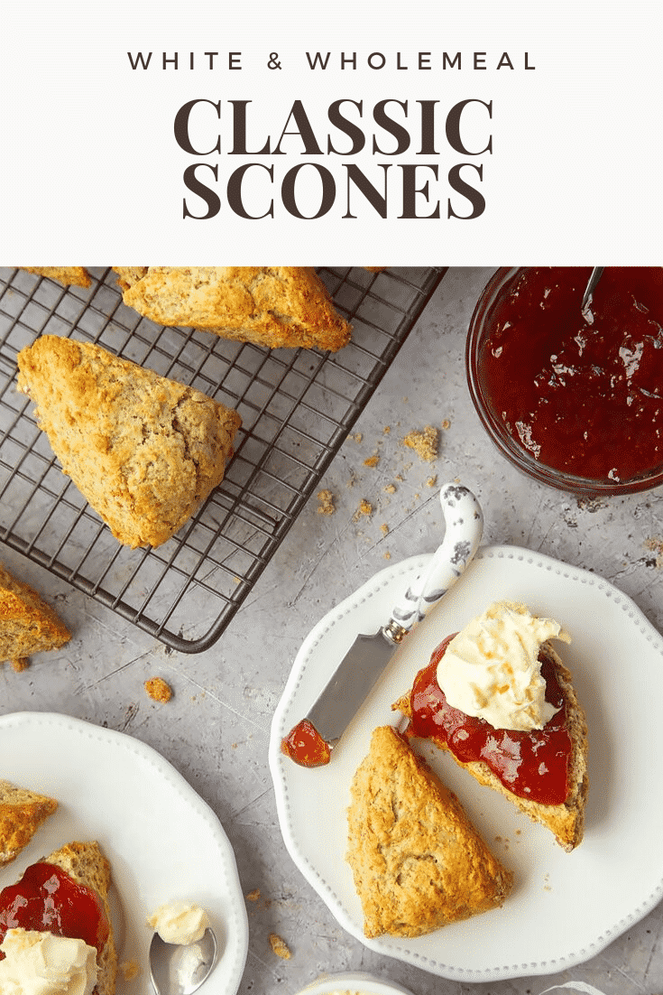 Overhead shot of a classic white and wholemeal scone on a decorative plate covered in jam and cream. At the side there's a decorative butter knife with some left over jam. At the top of the image there's some text describing the image for Pinterest.