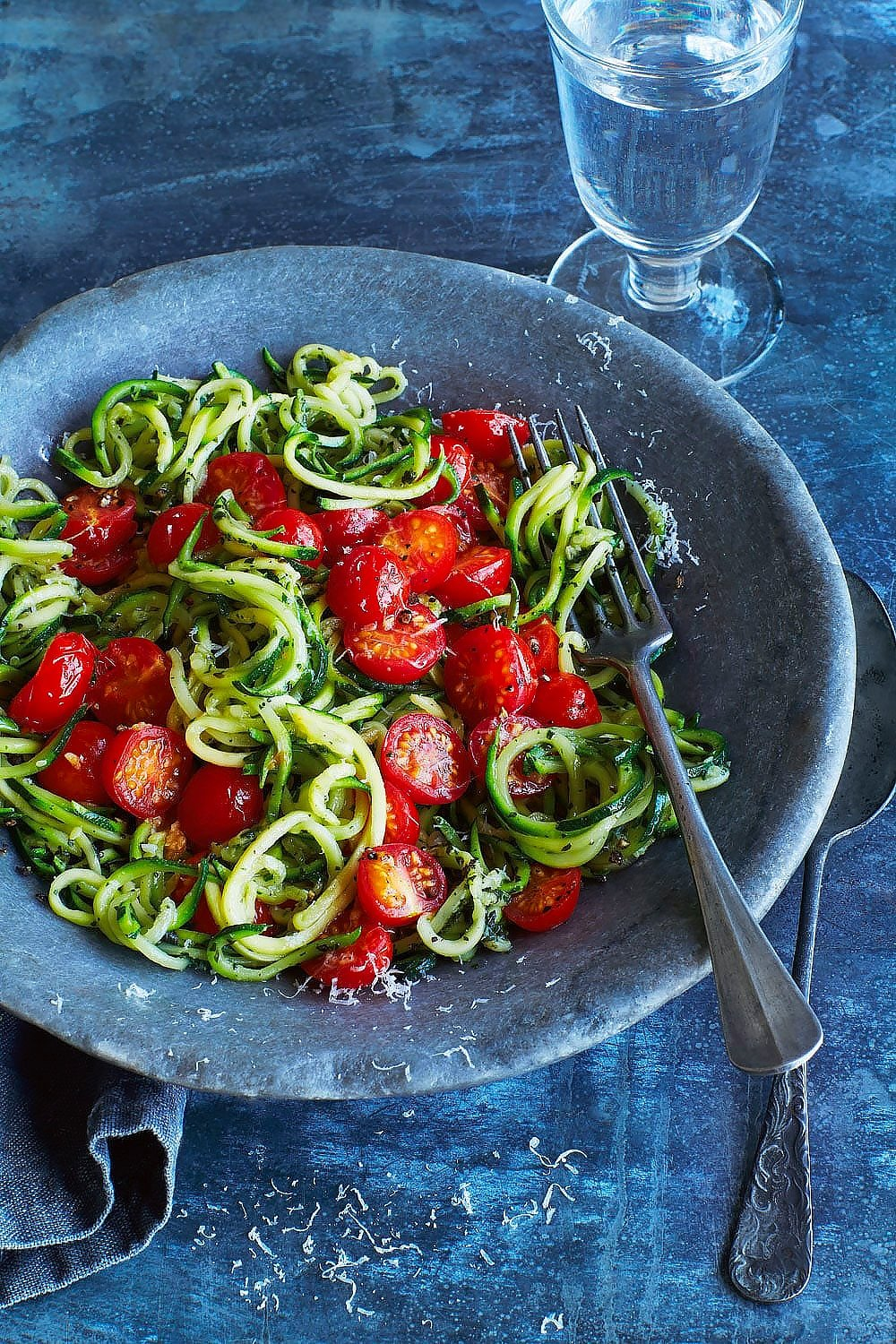 Annabel Karmel's courgette spaghetti, served into a bowl with a fork and spoon and a glass of water.