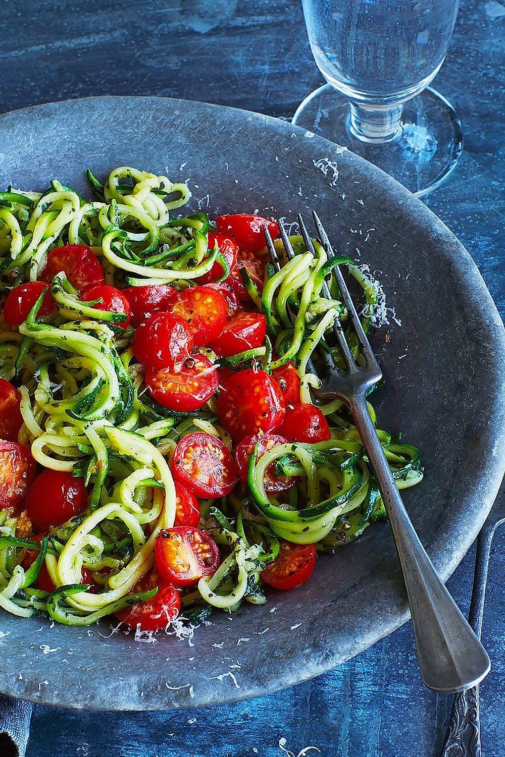 Annabel Karmel's courgette spaghetti, served into a bowl with a fork and a glass of water. Close up
