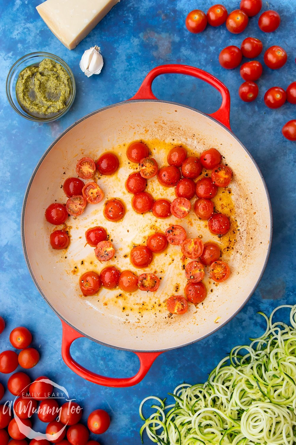 Cherry tomatoes, garlic, olive oil, black pepper and spiralised courgette in a frying pan - the tomatoes have been briefly cooked