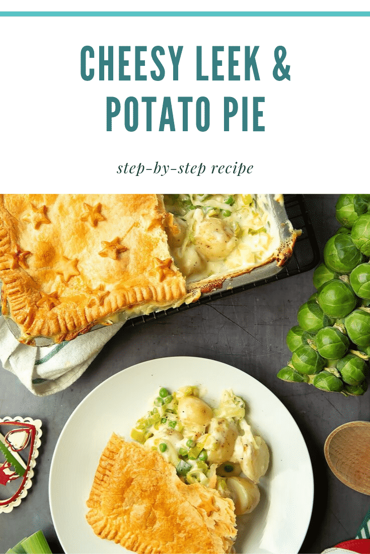 Overhead shot of a plate of cheesy leek and potato pie next to some of the ingredients required to make the recipe. At the top of the image there is some teal text describing the image for Pinterest.
