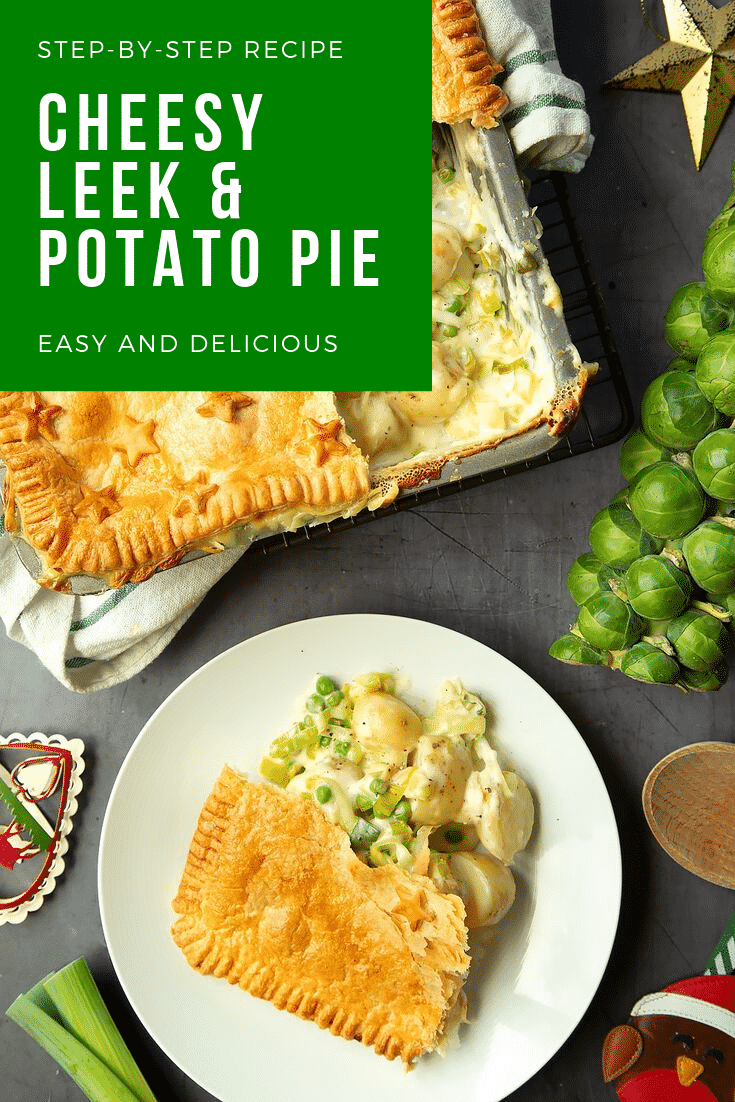 Overhead shot of a plate of cheesy leek and potato pie next to the tray in which it has been baked. Both items sit on a dark grey table. At the top of the image there is some white text on a green background describing the image for Pinterest.