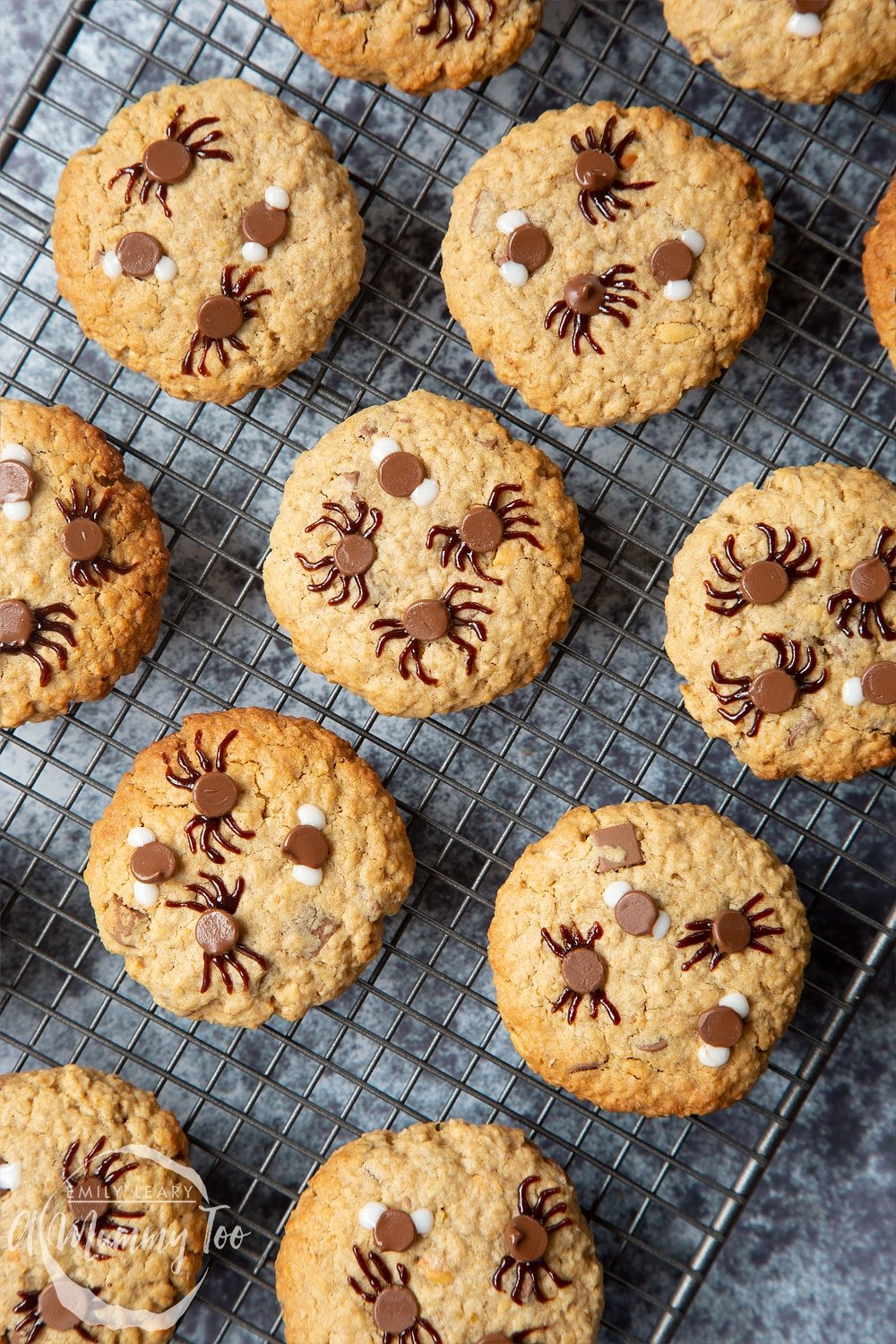 Halloween peanut butter spider cookies cooling on a wire rack and another set arranged on a plate.