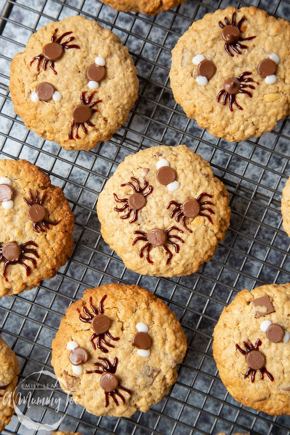 Full decorated Halloween peanut butter spider cookies on a wire rack.