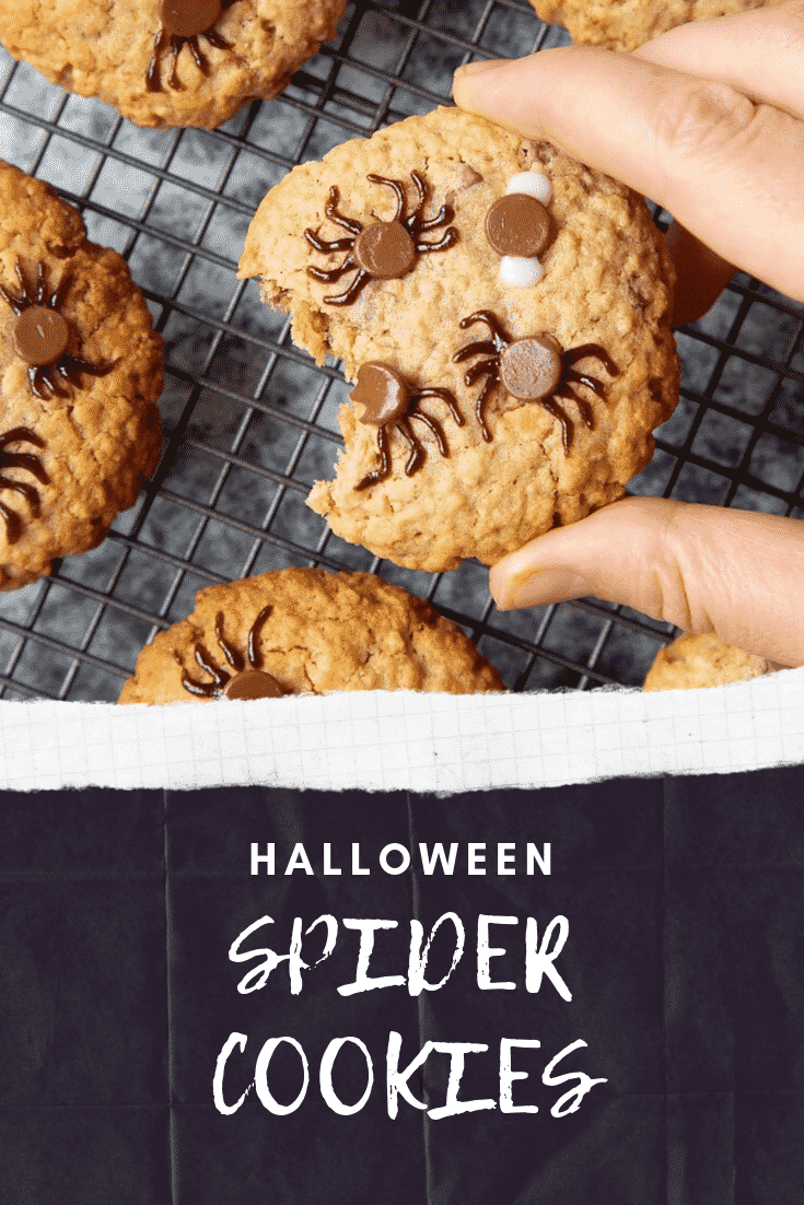 A hand is lifting up a Halloween peanut butter spider cookie from a cooling rack filled with them. A bite has been taken from from the cookie.