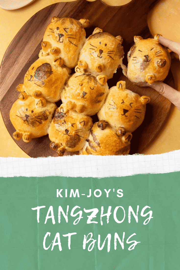A set of 9 tangzhong bread buns shaped to look like kittens. A hand tearing one bun away.