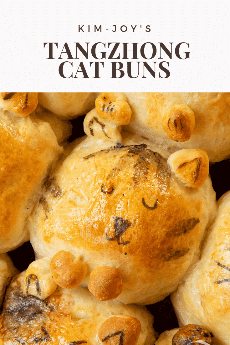 A close up of 9 tangzhong bread buns shaped to look like kittens. The kitten in the centre is smiling and sleeping.