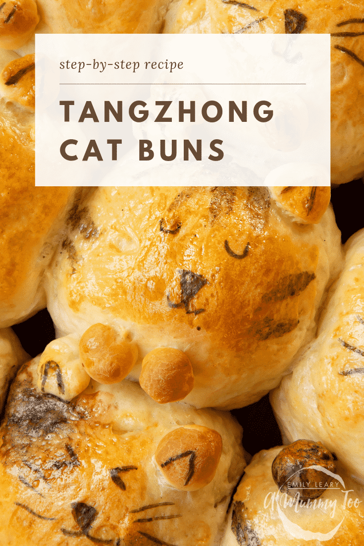 A close up of 9 tangzhong bread buns shaped to look like kittens. The kitten in the centre is smiling.