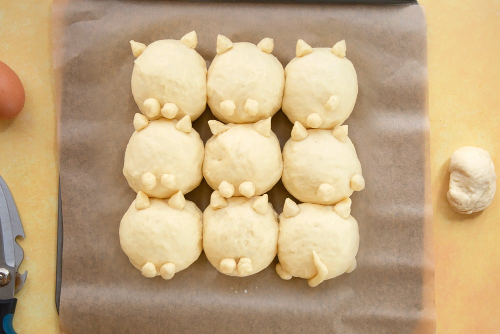 9 balls on tangzhong bread dough arranged on a tray lined with baking paper. Cats ears, feet and tails made from dough and attached to the rolls.