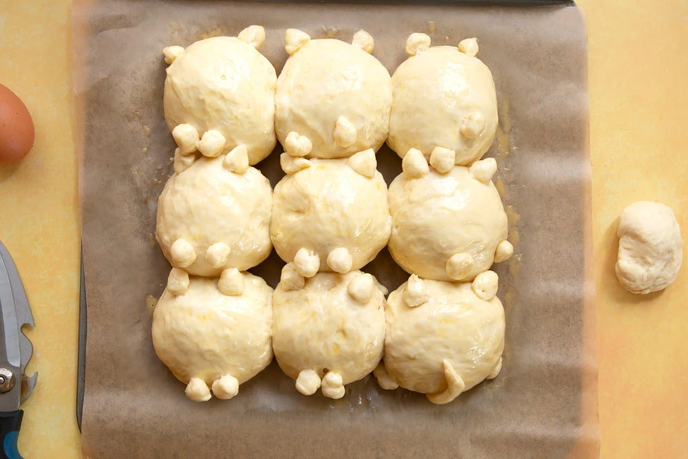 9 cat shaped tangzhong bread rolls on a tray lined with baking paper. Proved and brushed with egg wash.