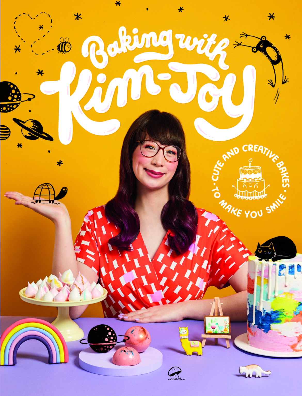 Book cover: Baking with Kim-Joy. Shows the author sitting at a table surrounded by her bakes
