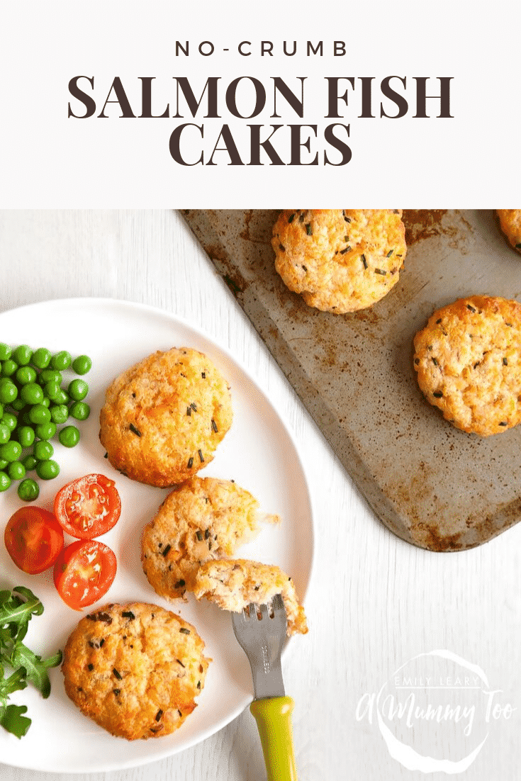 Overhead shot of some salmon fish cakes. One set is on a plate with a side of veg and a fork cutting into them. The other set is on a baking tray. Both items are on a white wooden background. At the top of the image there's some text describing the image for Pinterest.