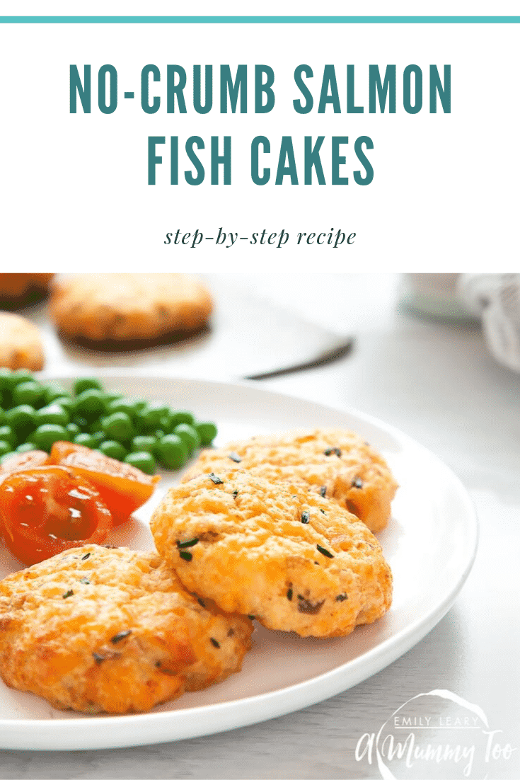 Close up of three salmon fish cakes on a white plate with vegetables. In the background you can see some additional salmon fish cakes on a baking sheet. At the top of the image there's some text describing the image for Pinterest.