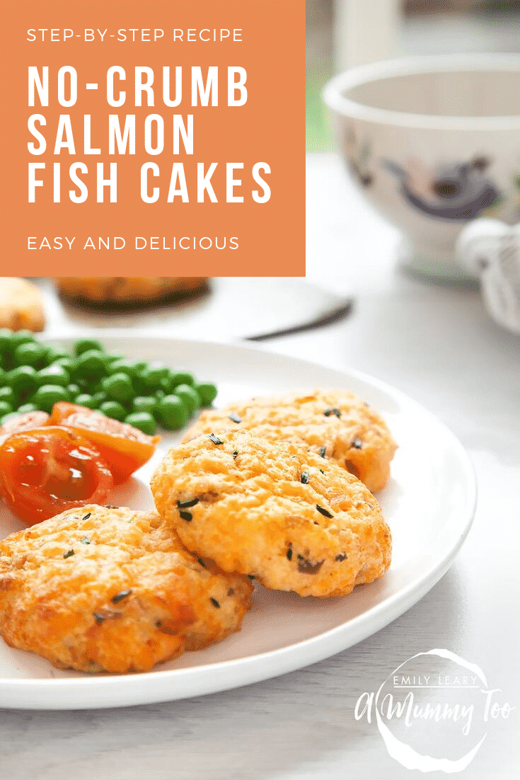 Three salmon fish cakes sit on a plate with some chopped cherry tomatoes and peas. The plate sits on a white wooden background with some additional salmon fishcakes on a baking tray in the background. At the top left hand side there's some text describing the image for Pinterest.