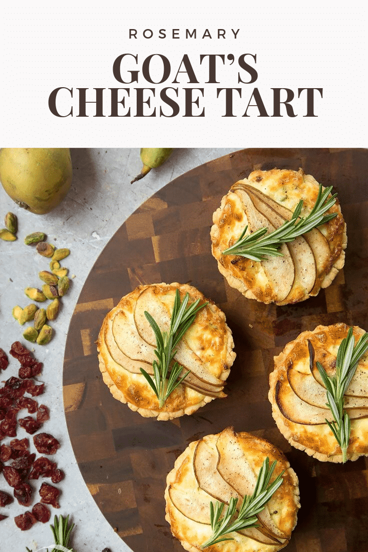 Overhead shot of four rosemary goat's cheese tarts on a wooden board with some of the ingredients required to make the dish on the side. At the top of the image there's some text describing the image for Pinterest.