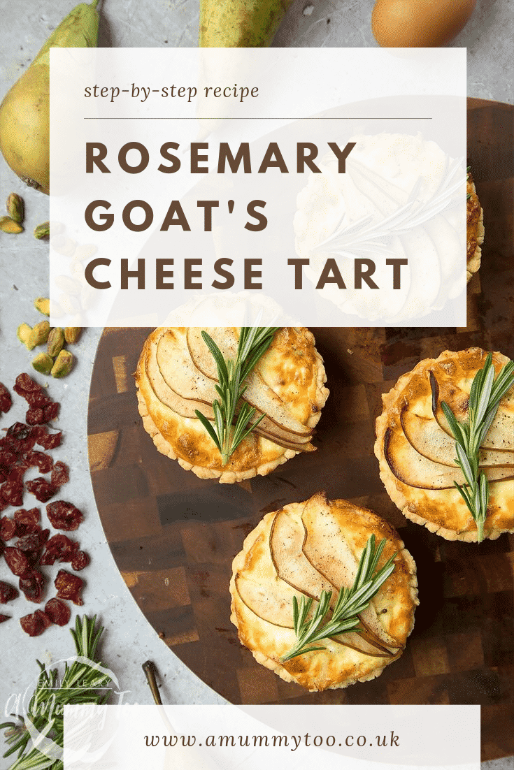 Overhead shot of four rosemary goat's cheese tarts on a decorative wooden circular board with different ingredients required for the recipe scattered at the side.