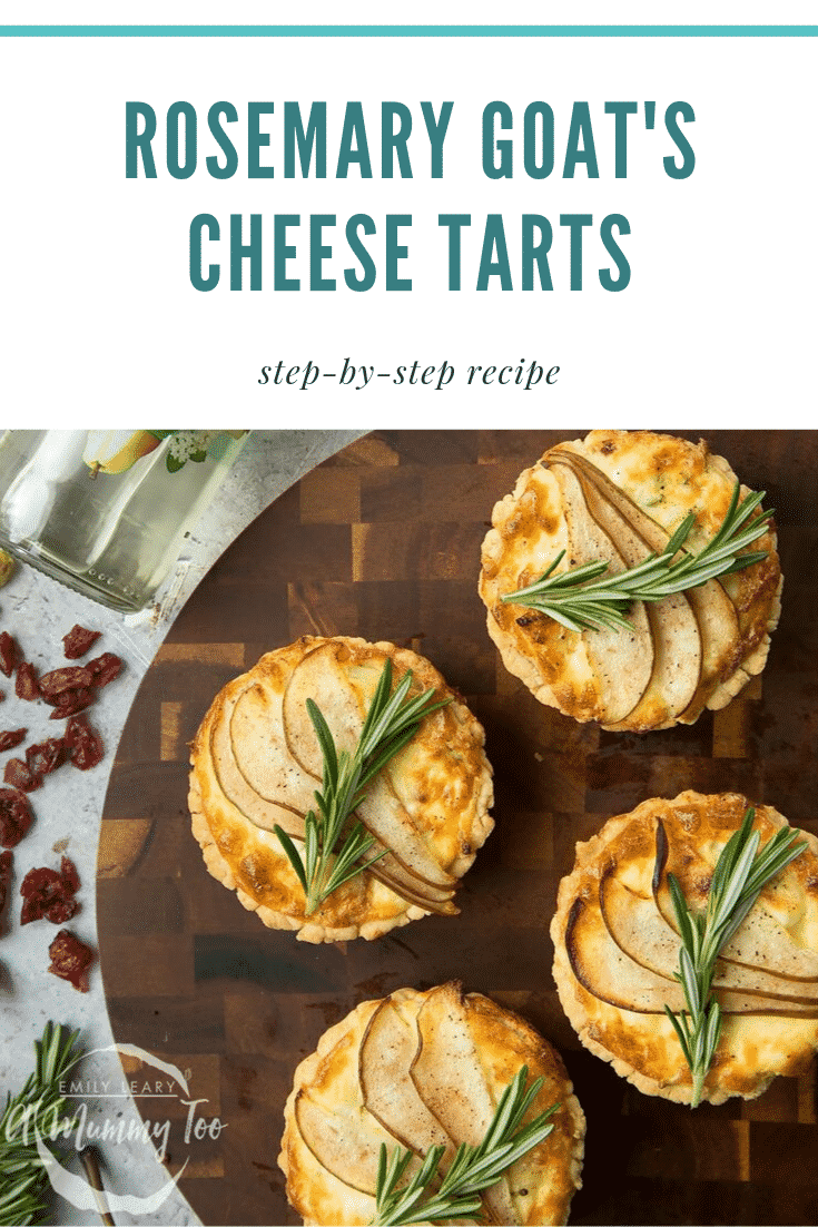 Overhead shot of four rosemary goat's cheese tarts on a wooden board. At the top of the image there's some teal text describing the image for Pinterest.