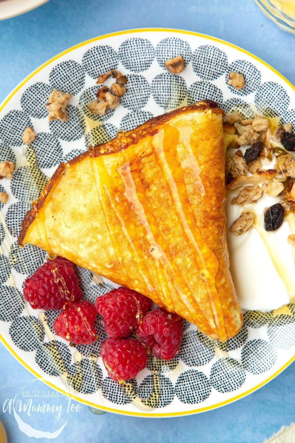 Sweet omelette served onto a plate with raspberries, yogurt, granola and honey