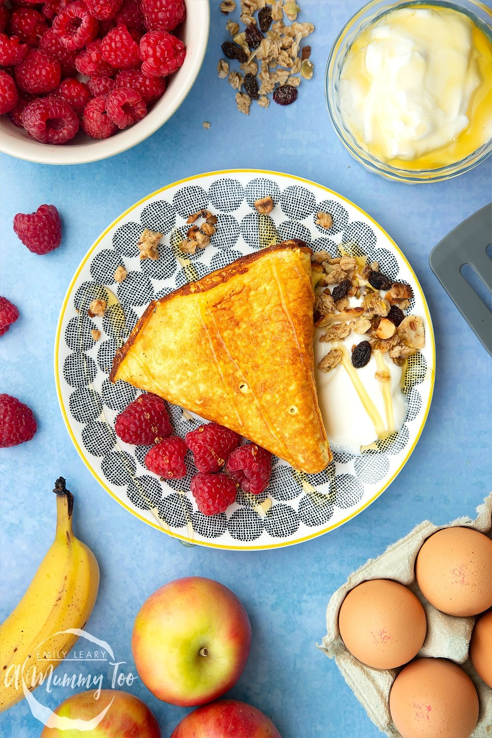 Sweet breakfast omelette on a plate with granola, yogurt and raspberries, drizzled with honey