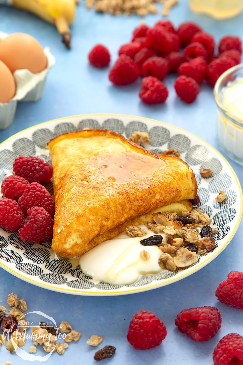 Sweet breakfast omelette, folded and served to a plate with yogurt, granola and raspberries