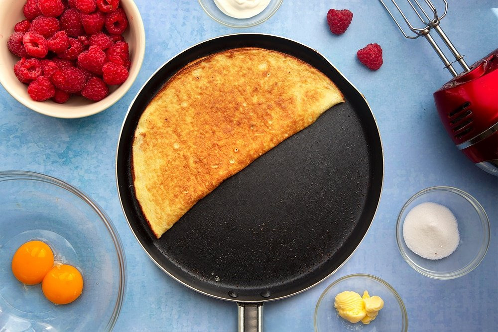 Large nonstick pan containing a cooked sweet omelette, folded in half