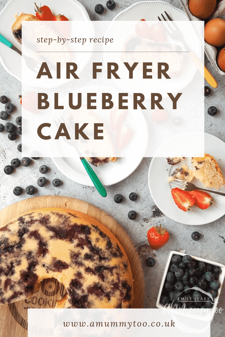 Overhead shot of a blueberry cake cooked in the ActiFry on a wooden board. At the side there are four plates with slices of blueberry cake. At the top of the image there's some text describing the image for Pinterest.