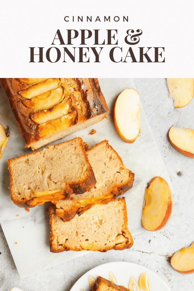 Overhead shot of the sliced cinnamon apple and honey cake on a white table. At the top of the image there's some brown text describing the image for Pinterest.