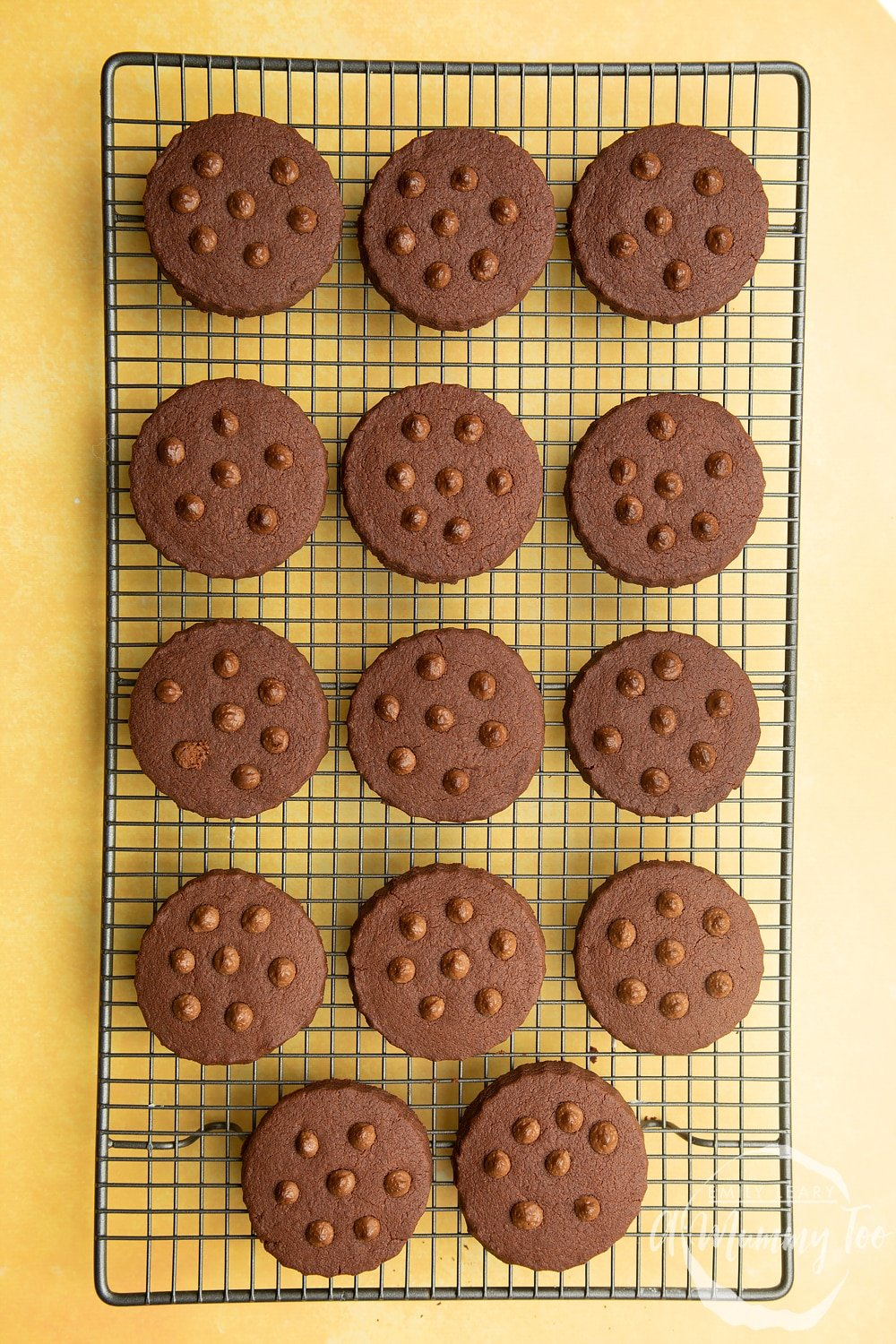 Chocolate shortbread cookies with chocolate chips cooling on a wire rack.