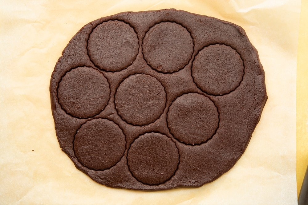 Chocolate shortbread dough rolled out on baking paper. Rounds cut into the dough with a cookie cutter.