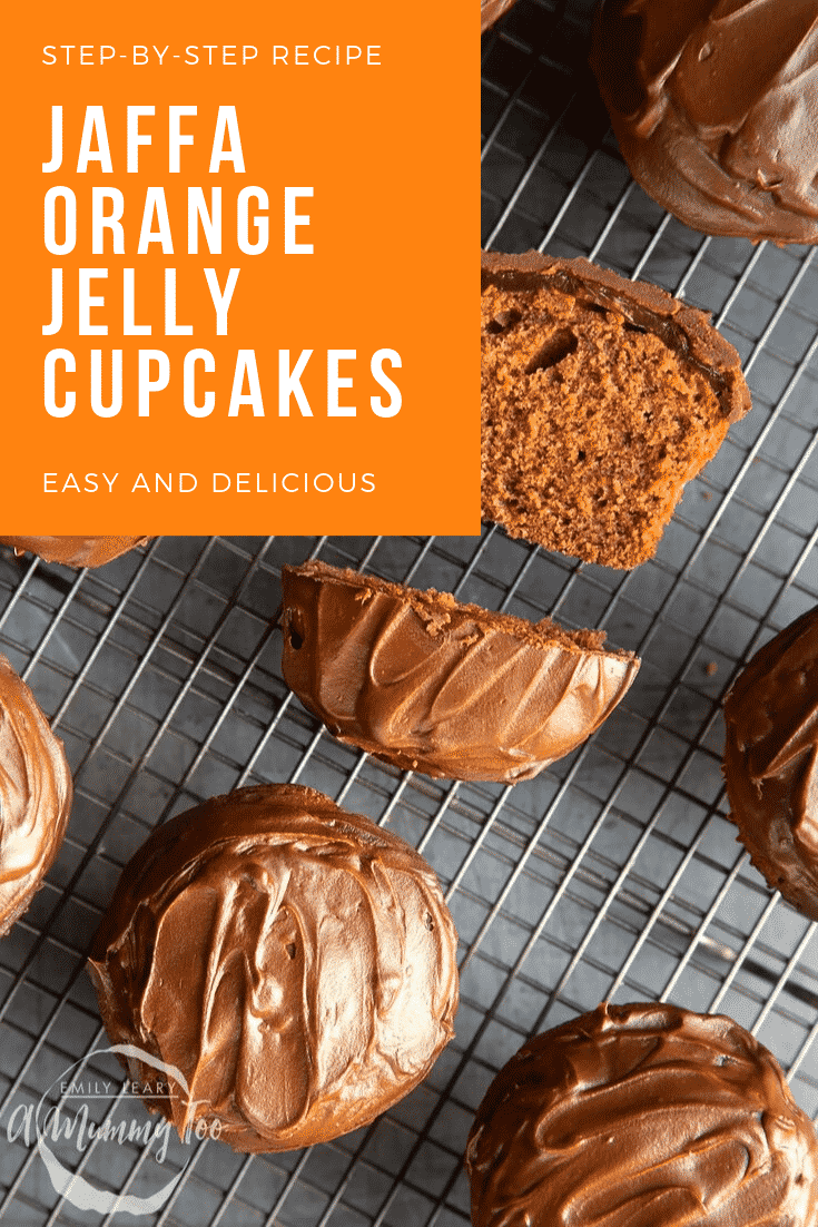 Overhead shot of the finished jaffa orange jelly cupcakes cooling on a wire rack. In the top left hand corner there's some white text on an orange background describing the image for Pinterest.