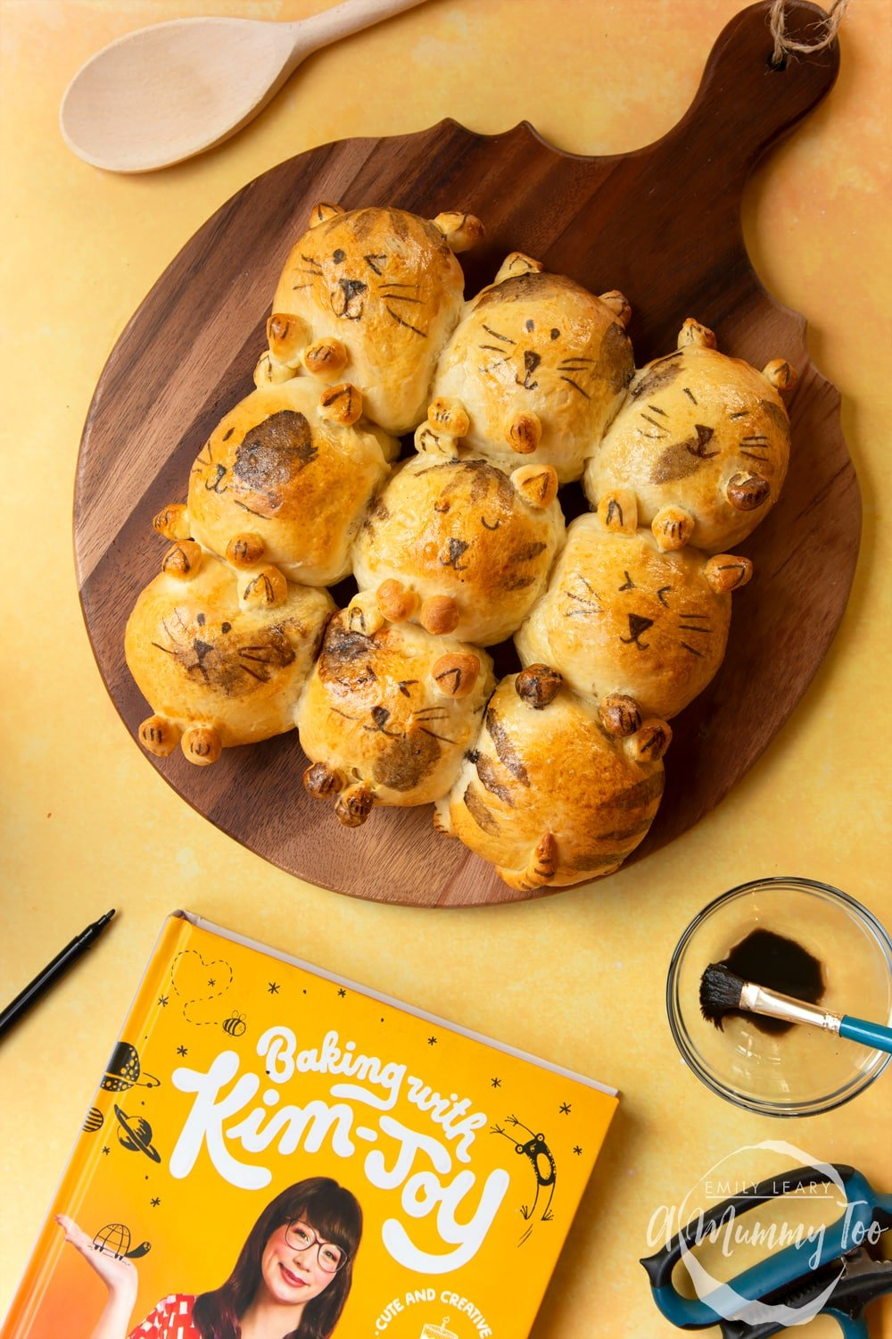 Kim-Joy's Tangzhong Cat Buns - nine bread rolls on a board, shaped and decorated to resemble cats.
