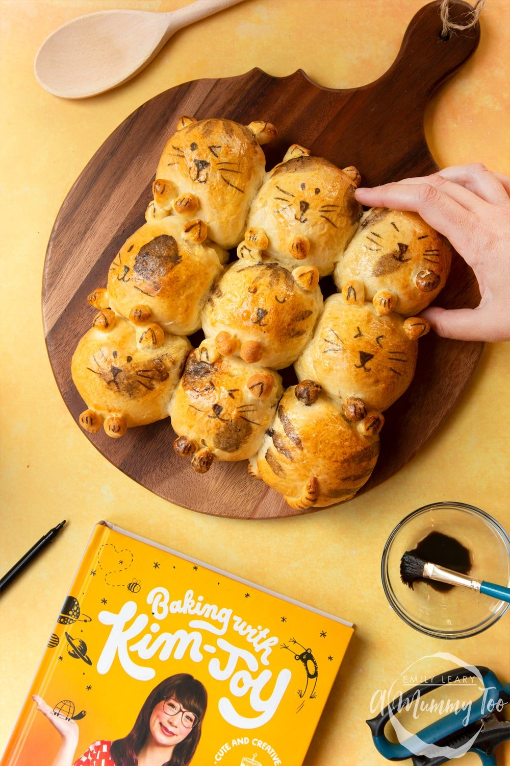 Kim-Joy's Tangzhong Cat Buns - nine bread rolls on a board, shaped and decorated to resemble cats, a hand reaches for one bun.