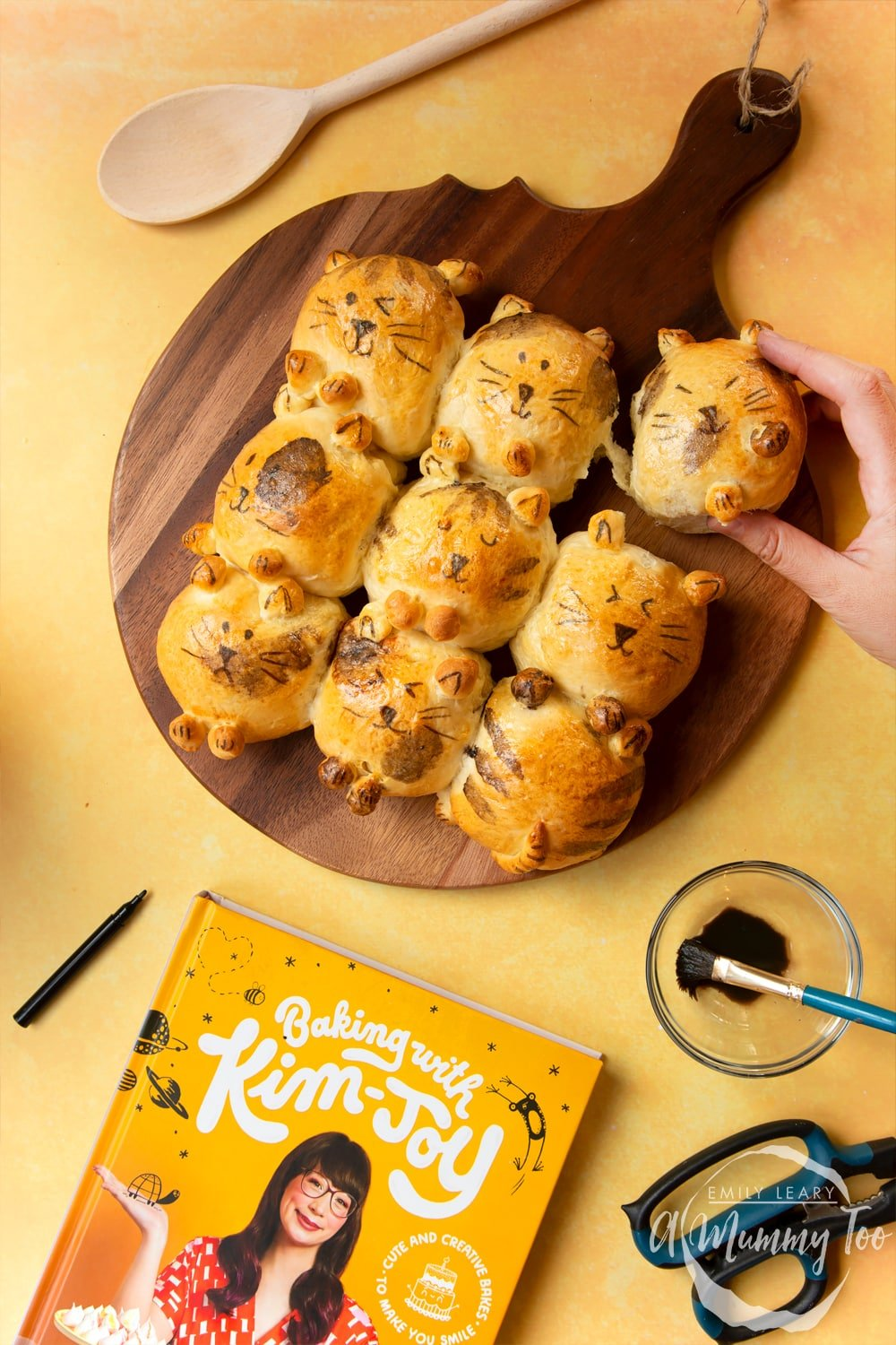 Kim-Joy's Tangzhong Cat Buns - nine bread rolls on a board, shaped and decorated to resemble cats A hand tears away one bun.