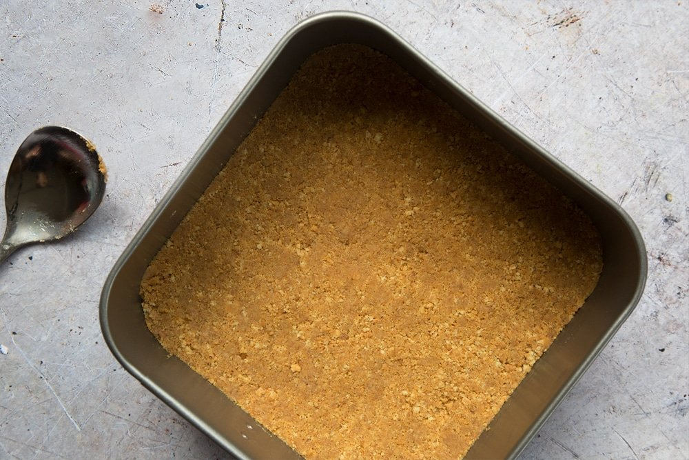 Overhead shot of digestive biscuits crust in a square loose-bottomed straight-sided tin and a spoon on the side